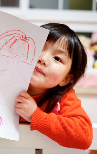 A small girl showing her art work
